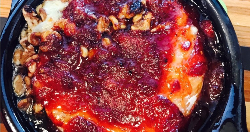 Baked bried with glazed strawberries and walnuts on top