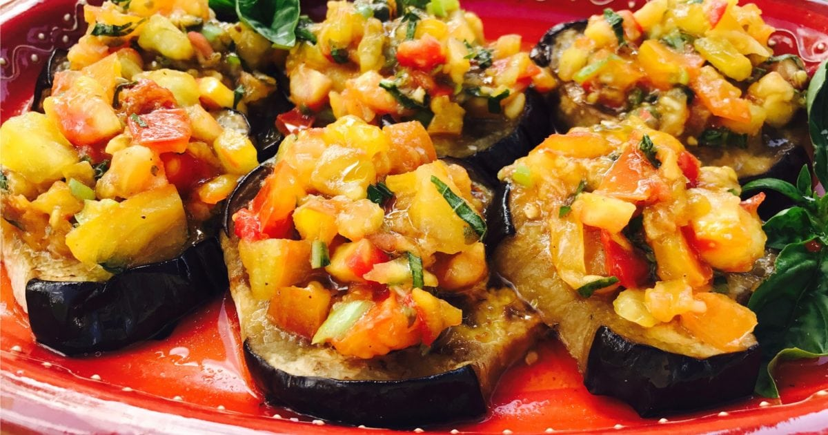 Baked eggplant discs topped with tomato salsa on red platter